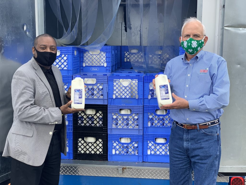 image shows two men wearing masks holding half gallons of mik in front of crates of milk